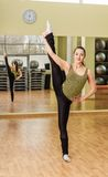 Young woman doing standing split in fitness class Stock Photos