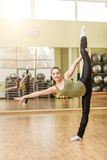 Young woman doing standing split in fitness class Stock Photo
