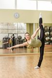 Young woman doing standing split in fitness class Royalty Free Stock Photography