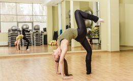 Young woman doing standing split in fitness class Stock Image