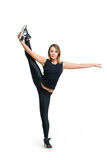 Young woman doing standing split isolated. Young slim sporty gimnast athletic flexible woman dancer in black sportswear doing standing split at fitness and dance stock image