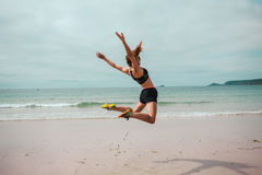 Young woman doing star jumps on the beach Stock Photography