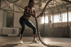 Fat burning workout using battle ropes. Young woman doing strength training using battle ropes at the gym. Athlete moving the ropes in wave motion as part of fat Stock Photo