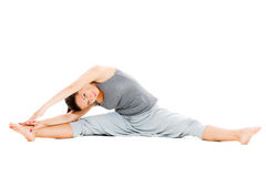 Young woman doing stretch exercise on floor Royalty Free Stock Photos