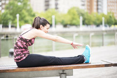 Young Woman Doing Stretches on wooden, bench. Stock Photo