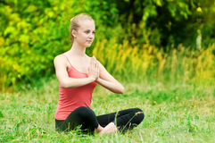 Young woman doing stretching exercise. Beautiful young woman doing stretching exercise on green grass at park. Yoga Royalty Free Stock Image