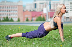 Young woman doing stretching exercise on grass Royalty Free Stock Images