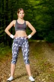 Young woman doing stretching exercise on road forest Stock Image