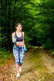 Young woman doing stretching exercise on road forest Stock Photo