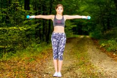 Young woman doing stretching exercise on road forest Stock Photos