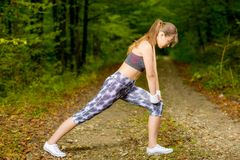 Young woman doing stretching exercise on road forest Stock Images