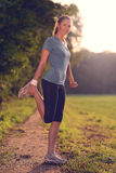 Young woman doing stretching exercises. As she limbers up her muscles to go on a jog or begin a workouts standing over a country track in golden light smiling Royalty Free Stock Photo