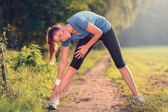 Young woman doing stretching exercises. As she limbers up her muscles to go on a jog or begin a workouts standing over a country track in golden light smiling Stock Photography