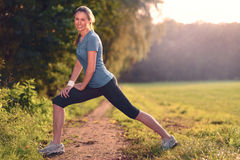Young woman doing stretching exercises. As she limbers up her muscles to go on a jog or begin a workouts standing over a country track in golden light smiling Royalty Free Stock Photos