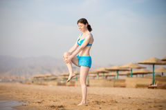 Young woman doing stretching exercises on the beach Stock Photos