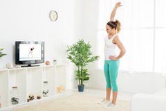 Young Woman Doing Stretching Exercises. Beautiful young women doing stretching exercises at home in front of the tv Royalty Free Stock Images