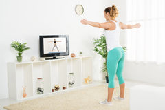 Young Woman Doing Stretching Exercises. Beautiful young women doing stretching exercises at home in front of the tv Royalty Free Stock Image