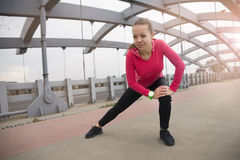 Young woman doing stretching exercises on the bridge Stock Photos