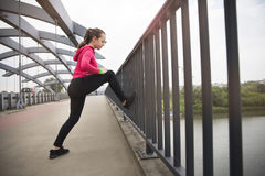 Young woman doing stretching exercises on the bridge Royalty Free Stock Photos