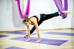 Young woman doing stretching exercises using the hammock. Aerial yoga. Stock Photo