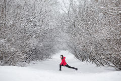 Young woman doing stretching exercises during winter. Training outside in cold snow weather in park. Trees in the snow. Weather snow cloud. Fitness on the Royalty Free Stock Image