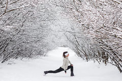 Young woman doing stretching exercises during winter Stock Image