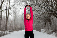 Young woman doing stretching exercises in winter Stock Photo