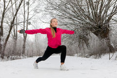 Young woman doing stretching exercises in winter. Young woman doing stretching exercises before workout in winter Royalty Free Stock Image