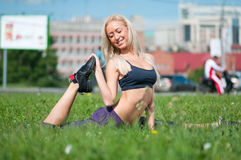 Young woman doing stretching on grass Stock Photo