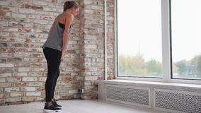 Young woman doing stretching of leg muscles leaning on window sill stock video footage