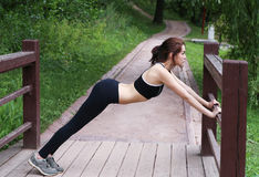 Young woman doing stretching outdoors. Young woman doing stretching outdoors in the afternoon. In the park Stock Images