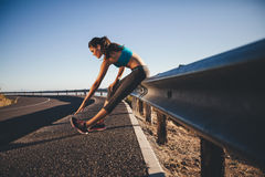 Young woman doing stretching after a run Royalty Free Stock Photos