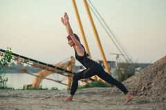 Young woman doing variation of high lunge yoga pose. Young woman doing variation of crescent yoga pose stock photos