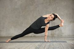 Young woman doing Visvamitrasana exercise. Young sporty woman practicing yoga, doing Visvamitrasana exercise, arm balance pose, working out, wearing sportswear stock images