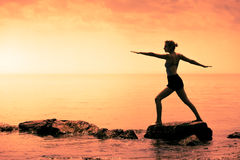 Young Woman doing the Warrior Yoga Position in Front of the Ocean. During Sunset royalty free stock photo