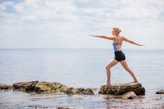 Young Woman doing Warrior Yoga Position Stock Photos