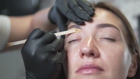 Young woman is doing a wax eyebrow correction at a beauty salon. The wizard applies gold wax to the bottom of the eyebrow and epilate extra hair stock video footage