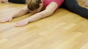 Young woman is doing wide-angle seated forward bend during yoga class in modern gym, slow motion. Blond lady in stylish sportswear is sitting with separated stock video footage