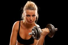Young woman doing workout. Athletic young lady doing workout with weights Royalty Free Stock Photo