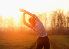 Young woman doing workout on the road at sunset. Royalty Free Stock Photography