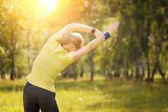 Young woman doing workout on the road at sunset. Stock Photos