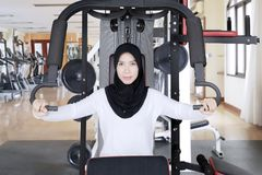 Young woman doing workout with weight machine. Young woman wearing sportswear and veil while doing a workout with weight machine in the gym center Royalty Free Stock Photo