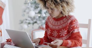Young woman doing Xmas shopping online. Young trendy African woman doing Xmas shopping online sitting in front of the decorated Christmas tree at home entering stock video