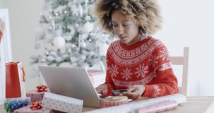 Young woman doing Xmas shopping online. Young trendy African woman doing Xmas shopping online sitting in front of the decorated Christmas tree at home entering stock footage