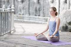 Young woman doing yoga in abandoned temple on wooden platform. Practicing. royalty free stock photos