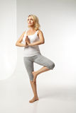 Young woman doing yoga against white background Stock Photo