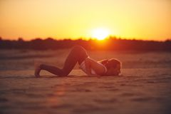 Young woman is doing yoga asana Ashtanga Namaskarasana - eight limbed salutation pose in the desert at sunset.  stock image