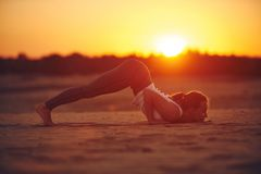 Young woman is doing yoga asana Ashtanga Namaskarasana - eight limbed salutation pose in the desert at sunset.  royalty free stock images