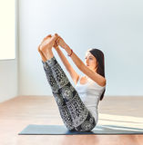 Young woman doing yoga asana both big toes pose Stock Image