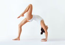 Young woman doing yoga asana bridge pose with right leg up. Ekopada Dhanurasana plus right Stock Photos
